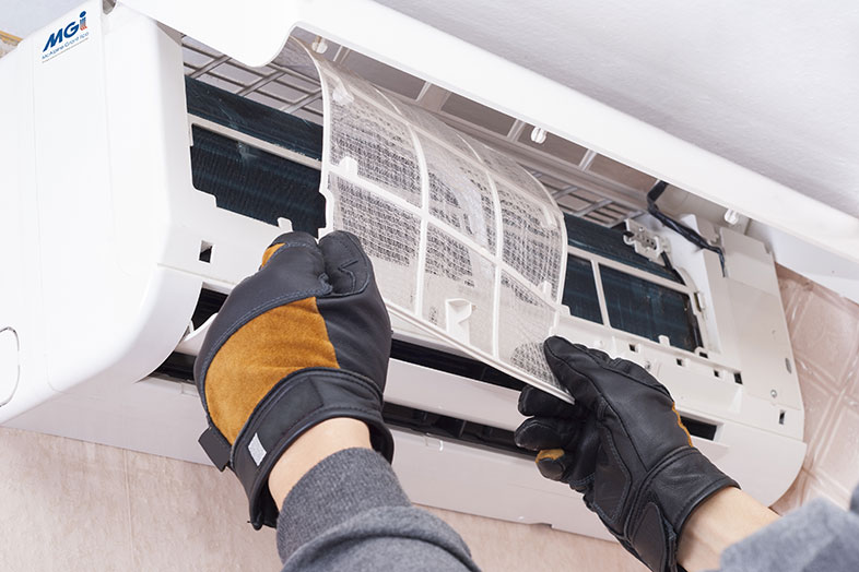 person servicing air conditioning unit