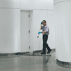 cleaner cleaning floor with wide mop