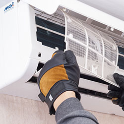 man replacing filter in air conditioning unit